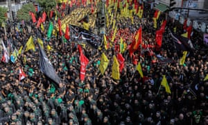 Hezbollah supporters carry their party flags in Beirut, Lebanon.