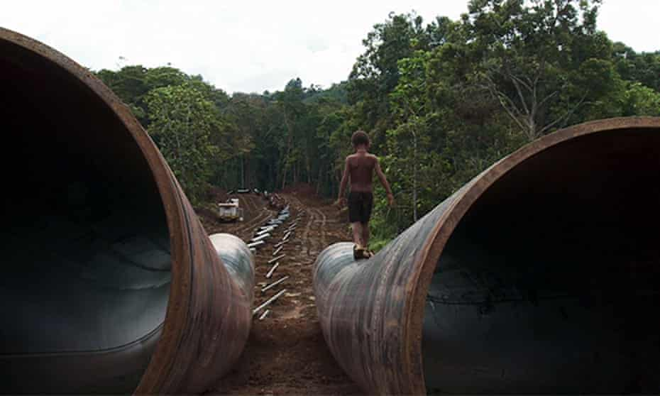 A boy walks on the Exxon Mobil LNG pipe in Papua New Guinea.