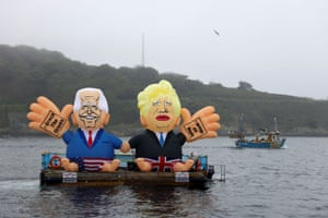 Inflatable dummies depicting President Biden and Boris Johnson are displayed on a boat at Gyllyngvase Beach in Falmouth by Crack the Crisis