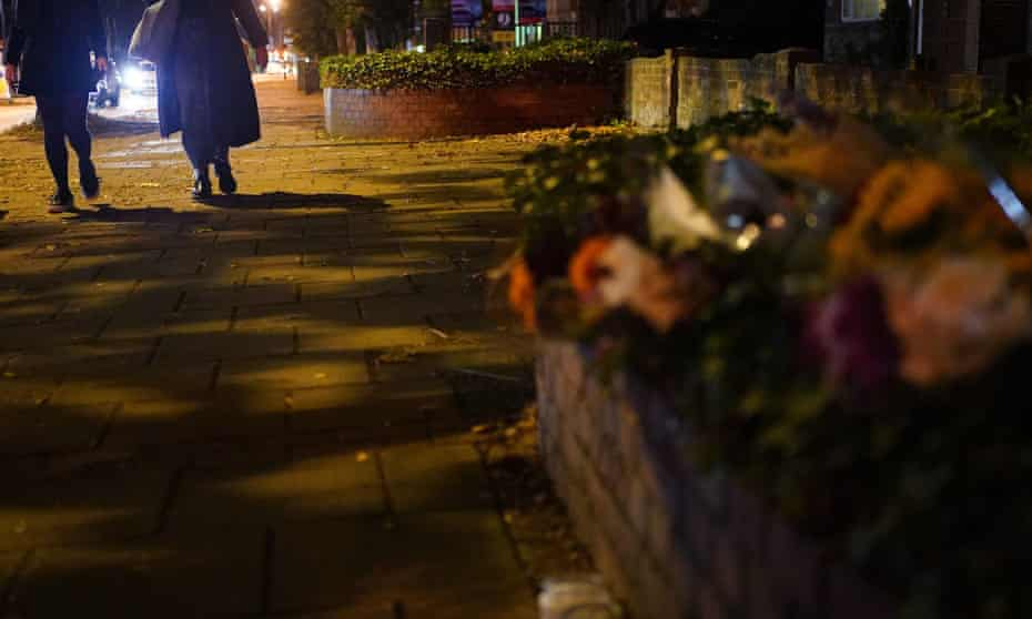 Women walk by floral tributes to Sarah Everard in Clapham, south London.
