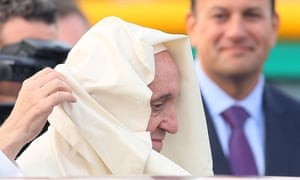 The wind catches the pontiff's pellegrina as he is escorted to his Shepherd One aircraft during a farewell ceremony at Dublin airport