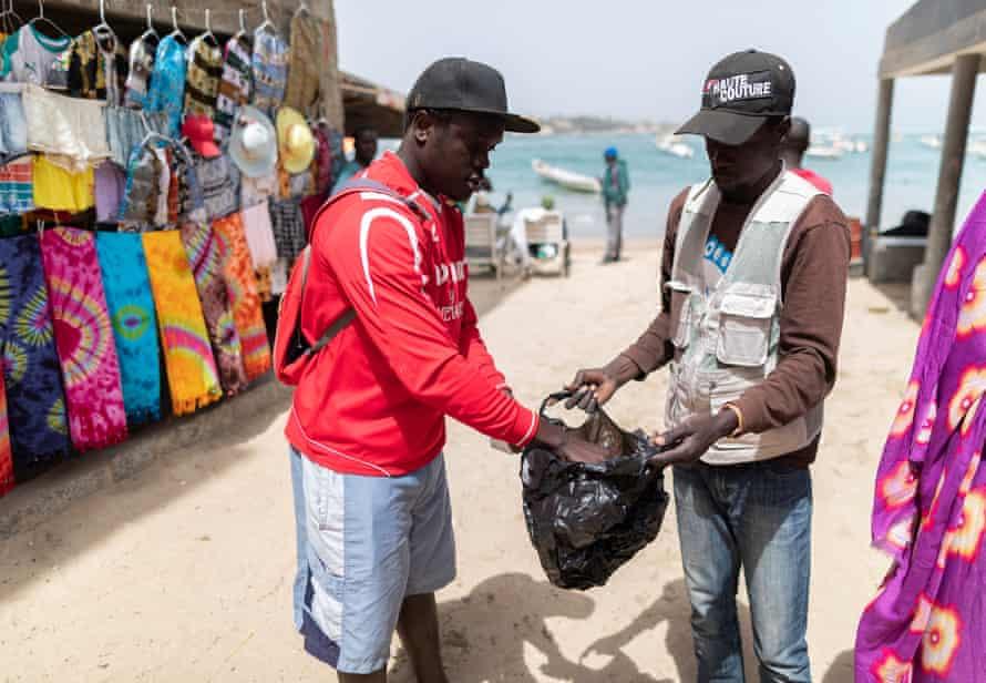 A vendor puts clothes in a single-use plastic bag in Ngor village in Dakar, Senegal
