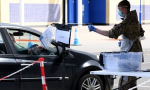 A man is handed testing equipment in his car in Leicester