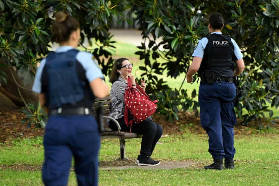 NSW Police officers ask people to move on while on patrol at Rushcutters Bay park in Sydney, Wednesday, April 1, 2020.