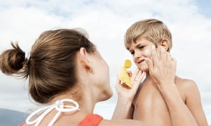 A mother applies suncream to her son