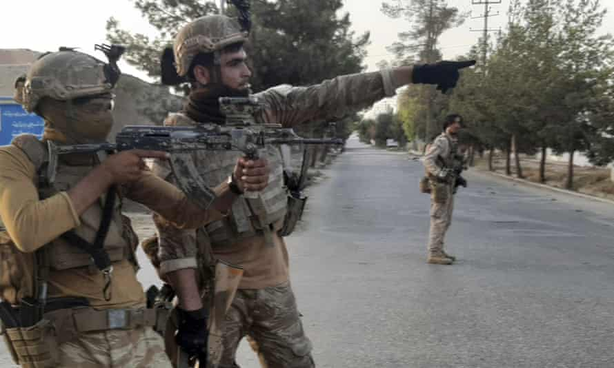 Afghan special forces patrol a deserted street during fighting with Taliban fighters in Lashkar Gah.