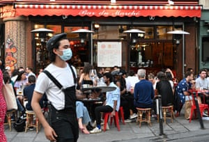 "A waiter wearing a face mask serves clients while people eat and have drinks on the terrace of the cafe-restaurant ""Le Bar du Marche"" in Paris, France on 02 June, 2020."