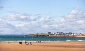 A large group of walkers on the beach at Elie.
