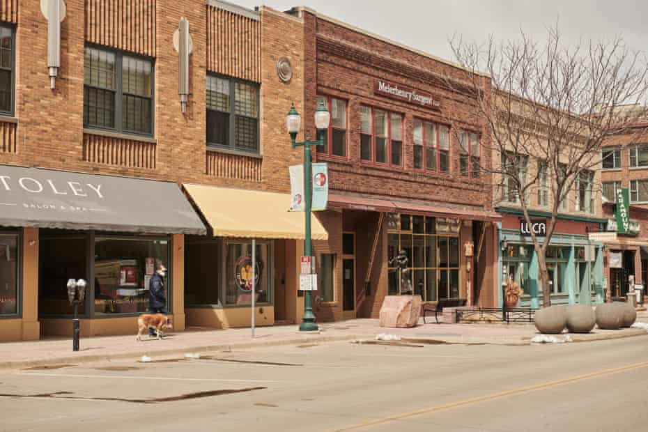 A pedestrian wearing a protective masks walks a dog past closed stores in downtown Sioux Falls, South Dakota, U.S., on Wednesday, April 15, 2020. South Dakota Governor Kristi Noem has argued that it would be pointless to enact a significant stay-at-home order, because it would need to be maintained until October. On Wednesday, South Dakota surpassed 1,000 confirmed Covid-19 cases.
