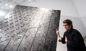 Artist Robert Longo speaks in front of his artwork.