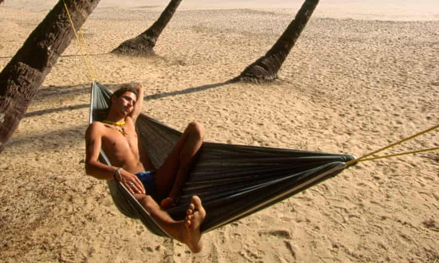 Man in hammock beside palm fringed beach in Goa, India