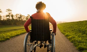 Woman in wheelchair in nature with sun setting