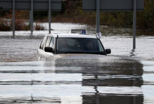 A Range Rover is driven out of flood waters after the River Don burst its banks in Rotherham