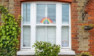 Children's rainbow posters in a house window