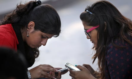 Girls engage with their mobile phones