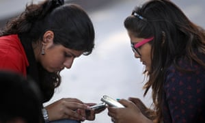 Girls in New Delhi use their mobile phones