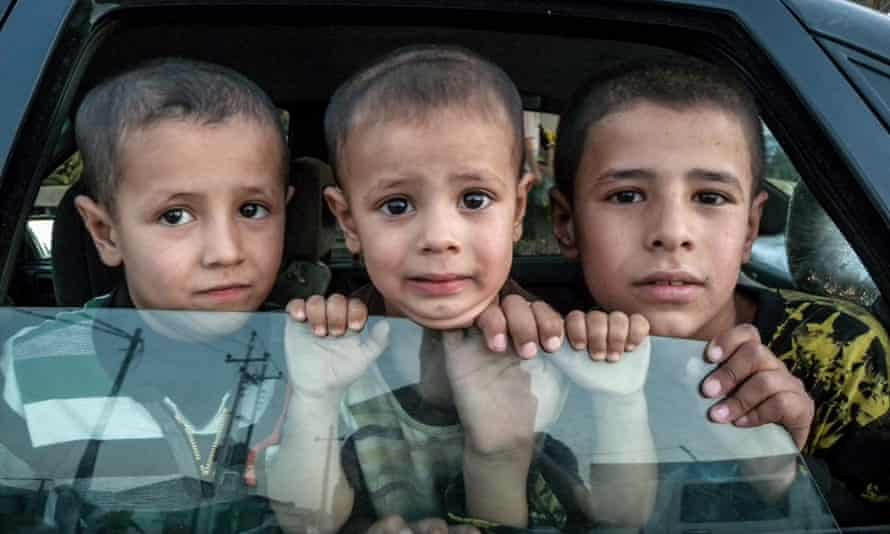 Kids look out of a car inside an all-Christian refugee camp in Erbil, Iraq.