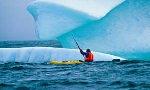 Conan Coates kayaking around an iceberg in the Atlantic Ocean along the Iceberg Alley near Hare Bay off Newfoundland