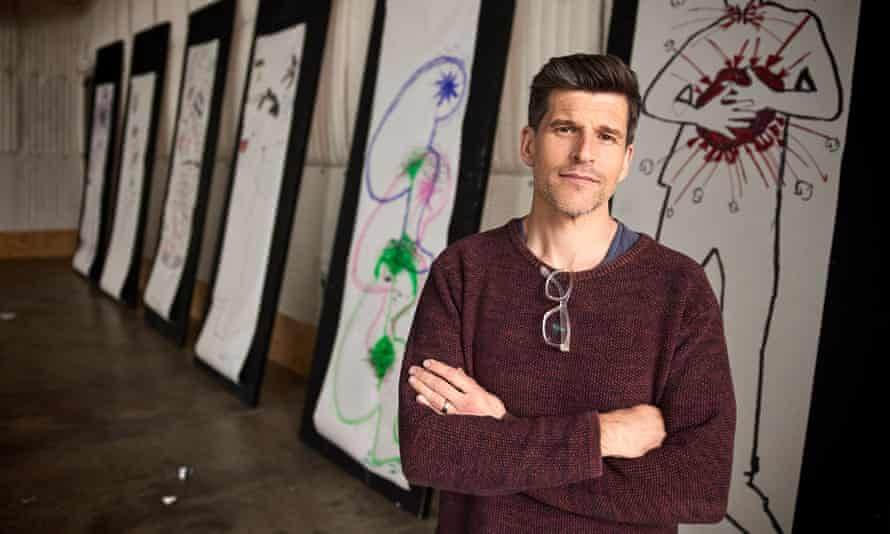 Osher Günsberg poses at an exhibition, with his 'virtue signalling' glasses