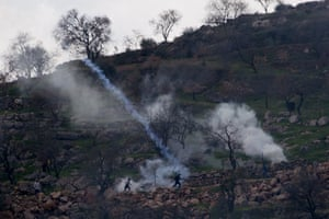 Israeli soldiers use teargas to disperse Palestinian protesters on the outskirts of the West Bank village of Mughayer.
