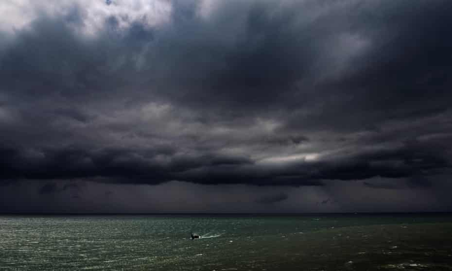 A fishing boat travels under dark clouds near the shores of Banda Aceh
