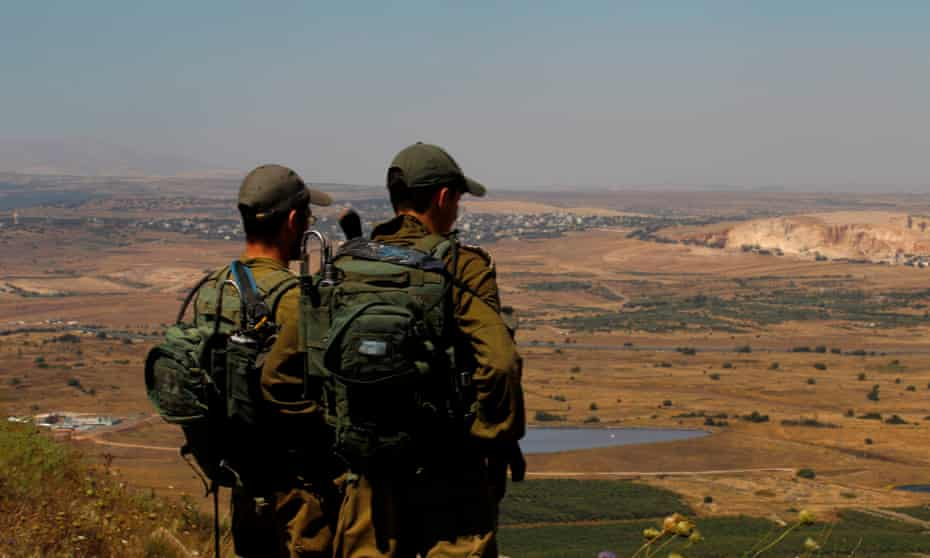 Israeli soldiers at an army base in the Golan Heights look out across the south-western Syrian province of Quneitra.