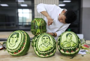 Chinese teacher Jiang Zhongmin shows watermelon carvings of (from left) Argentine football player Lionel Messi, French football player Kylian Mbappe and Portuguese football player Cristiano Ronaldo