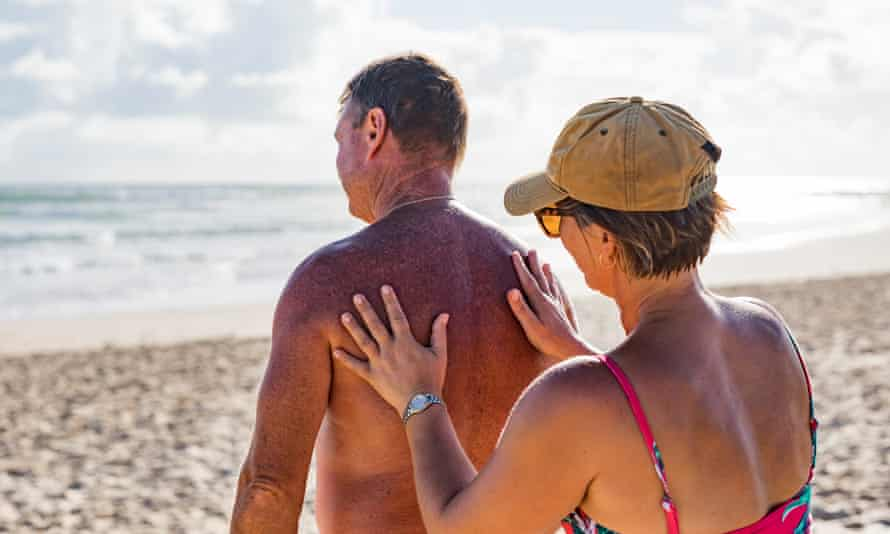 A couple apply sunscreen at the beach