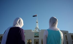 Visitors of Afghan nationality wearing hijabs are seen outside Parliament House in Canberra, 2 October 2014.