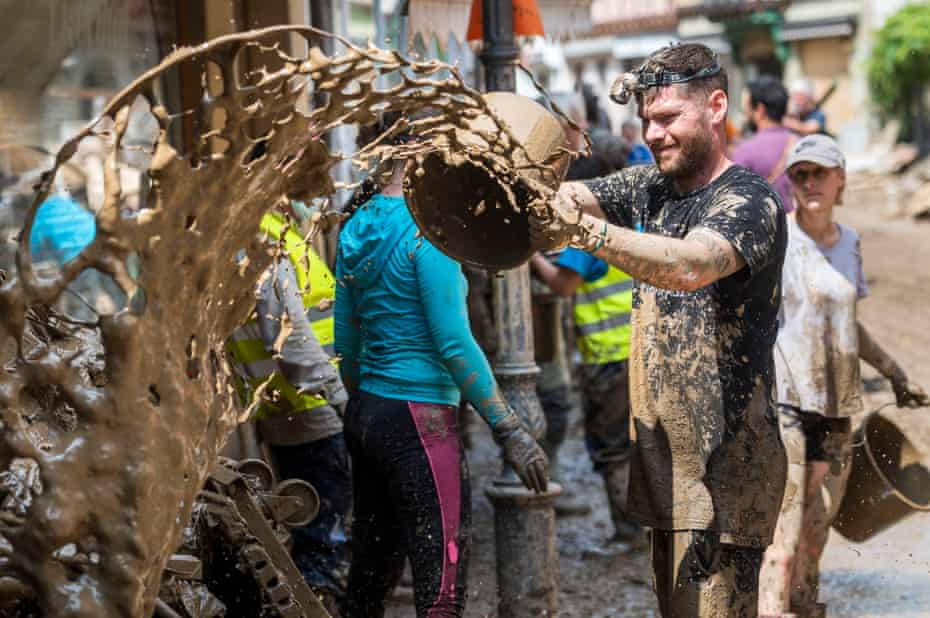 A helper removes mud from a residential building
