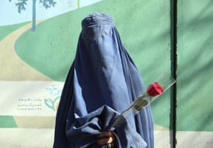 A woman holds a rose during an event marking International Women's Day in Kabul, Afghanistan