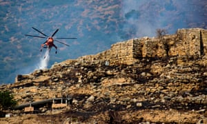 A firefighting helicopter drops water to extinguish flames during a wildfire near the archaeological site of Mycenae.