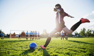 A photo of a teenage girl kicking a football towards a goal