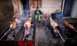 A Bosnian Serb boy roasts lamb and pig in the village of Vojkovici, near Sarajevo
