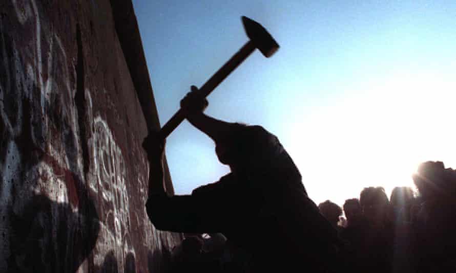 A man hammers away at the Berlin Wall, 12 November 1989