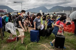 Travelers carry their luggage through protesters on the highway leading to Hong Kong International Airport on September 1, 2019