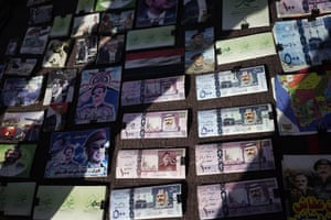 Play money (in Saudi riyals) and other war-related imagery at a market in Sana'a in June 2016.