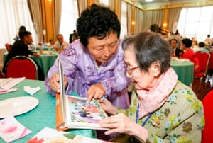 South Korean Han Sin-Ja (R, 99) and her North Korean daughter Kim Kyung-Young (71) talk as they look at family photos at Kumgangsan hotel in Mt. Kumgang resort.