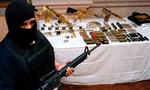 An officer from Mexico's federal police stands next to weapons seized from the Zetas cartel, partly funded by oil theft.