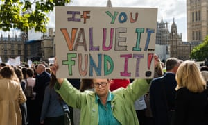 A headteacher protests against funding cuts in London.