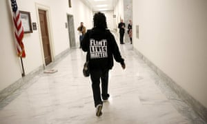 A woman with a Flint Lives Matter sweater walks to a hearing on the crisis