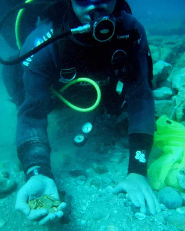 A scuba diver holds some of the gold coins recently found on the seabed in the ancient harbour in the Israeli town of Caesarea.