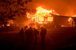 A firefighter carries a hose as a house burns