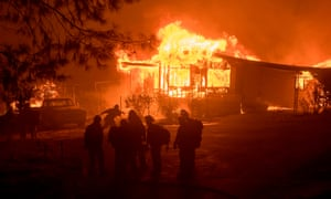 A firefighter carries a hose as a house burns in Oroville, California on Saturday.