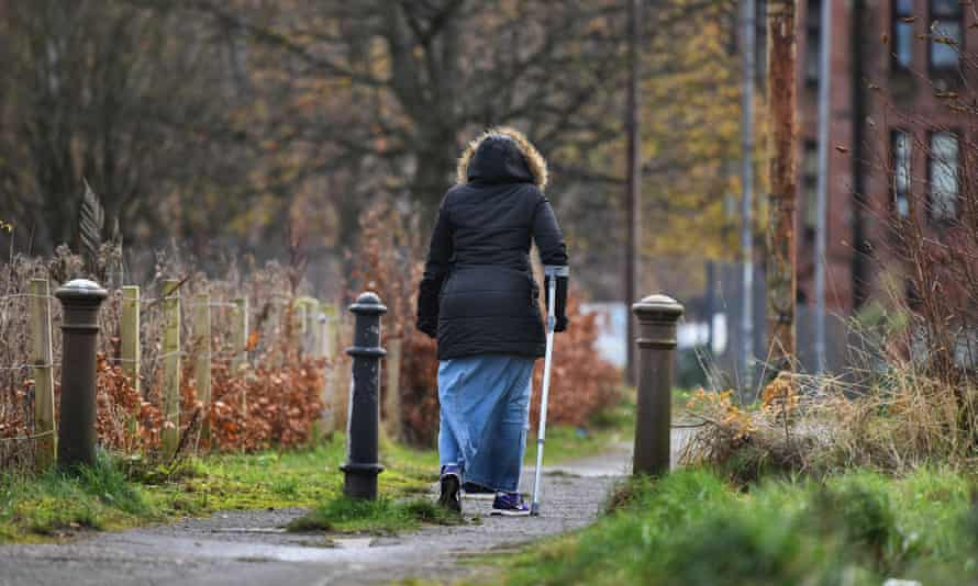 A woman walks through the Possilpark area of Glasgow