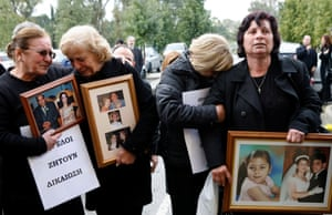 Victims' relatives hold pictures of their loved ones outside court, in February 2009.