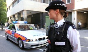 Woman police officer standing next to police car