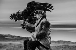 Black and white portrait of a young eagle hunter and his young eagle in the mountains of Mongolia.