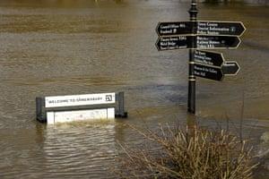 A sign board peeks above flood waters in Shrewsbury, Shropshire