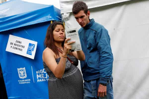 A Venezuelan couple read a flyer about vaccination in the Bogotá camp's registration area